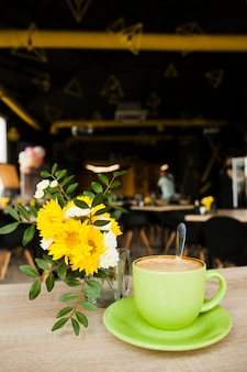 Tasty coffee near beautiful flower vase on wooden table
