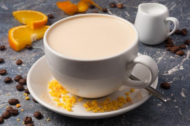 灰色の背景に牛乳とオレンジのおいしいコーヒー