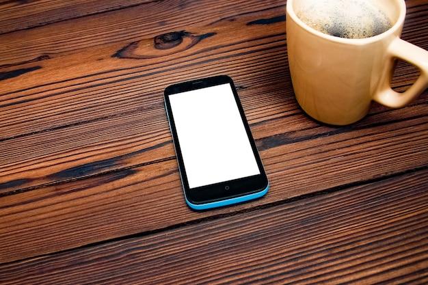 나무 테이블에 전화로 맛있는 커피