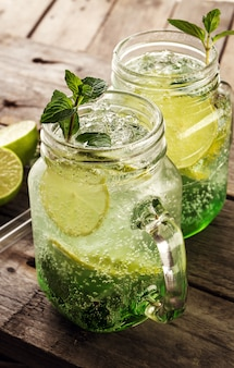 Tasty cold fresh drink lemonade with lemon, mint, ice and lime in glass on wooden table. closeup.