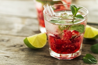 Tasty cold fresh drink lemonade with raspberry, mint, ice and lime in glass on wooden background. Closeup.