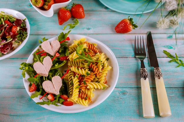 Tasty color rotini pasta with sausages, fresh strawberry on a wooden surface