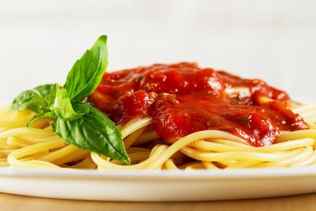 Pasta italiana di spaghetti cotti, saporita e saporita, con salsa di pomodoro bolognese e basilico fresco. avvicinamento.