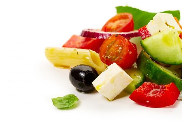 Ingredienti appetitosi colorati gustosi per insalata di verdure greca con penne di pasta su sfondo luminoso.