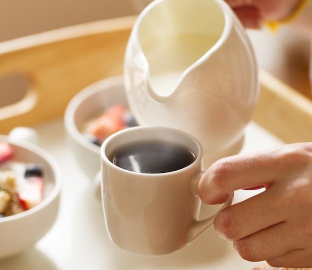白背景にオートミール、ヨーグルト、イチゴ、ブルーベリー、蜂蜜、ミルクとおいしいカラフルな朝食。ベッドでの朝食。閉じる。