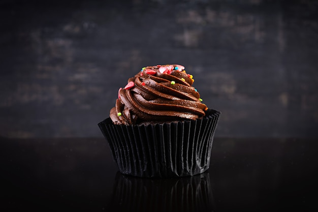 黒に分離されたおいしいカラフルなカップケーキ
