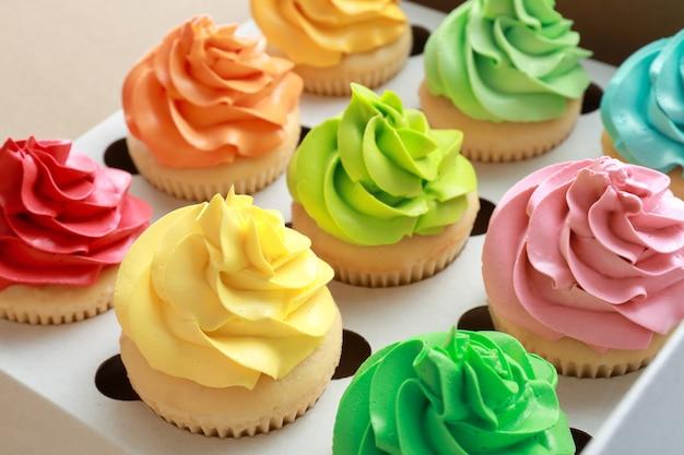 Tasty colorful cupcakes in cardboard box, closeup