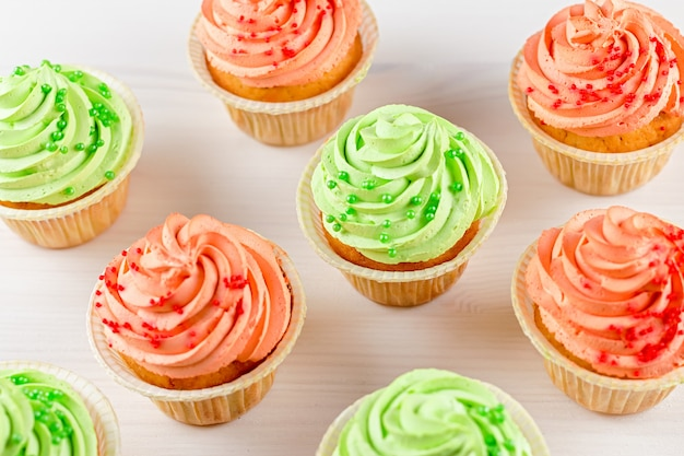 Tasty colorful cupcakes closeup on white woodentable, top view