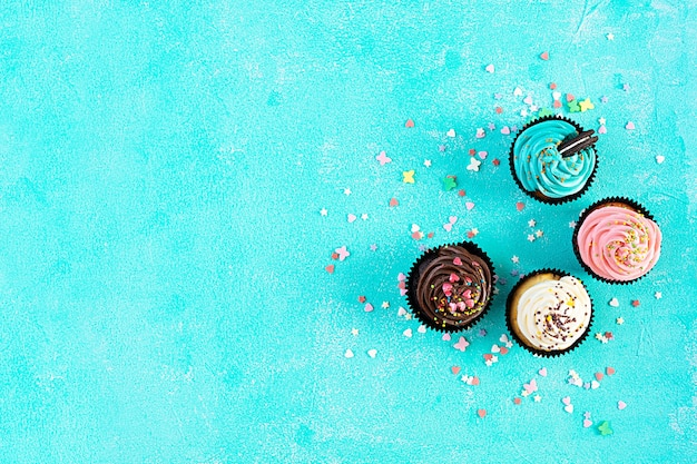 Tasty colorful cupcakes isolated on blue