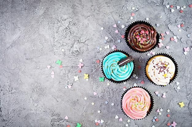 灰色で隔離のおいしいカラフルなカップケーキ