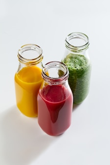 Tasty colorful fresh homemade smoothies in glass jars on bright background. closeup. healthy life, detox concept.