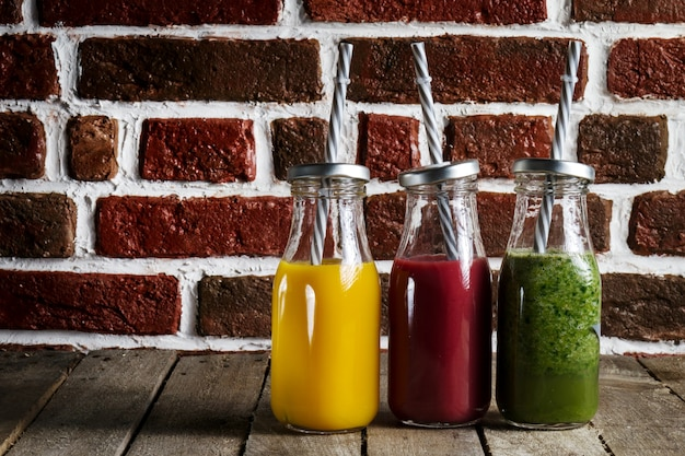 Tasty colorful fresh homemade smoothies in glass jars on wooden table. kitchen background.
