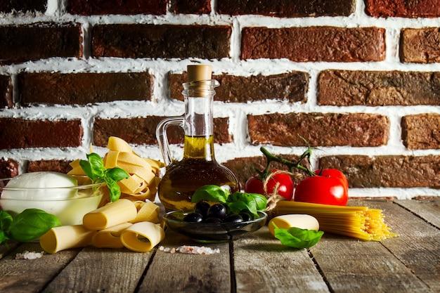 Gustoso concetto di cibo fresco variegato italiano con vari pasta spaghetti, formaggio mozzarella, basilico fresco, pomodori, olio di oliva, spezie. concetto di cottura. posto per il testo.