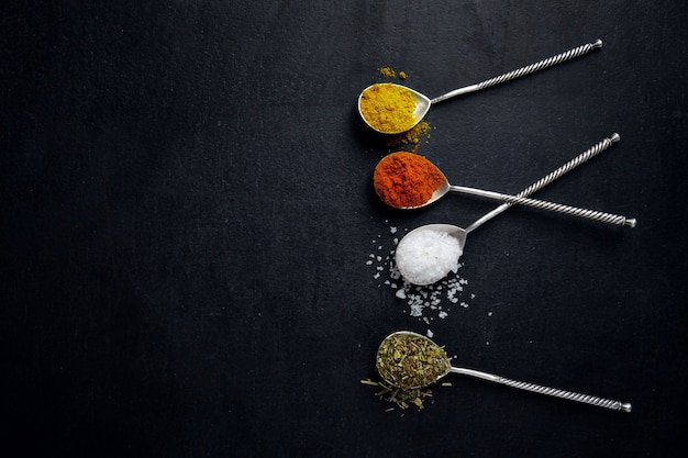 Tasty colorful spices in spoons on dark surface