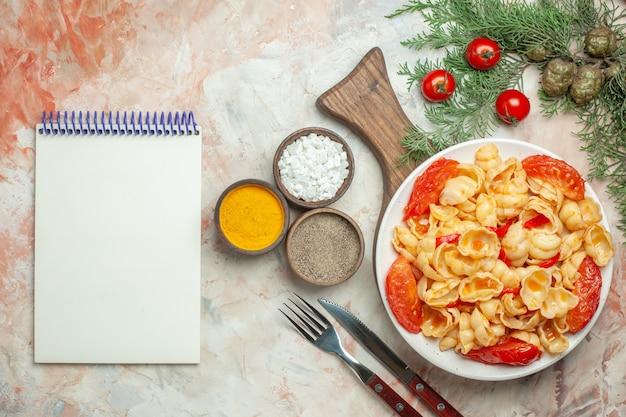 木製のまな板の白いプレートにおいしいコンキリエと混合色の背景にさまざまなスパイスとノートブックをナイフ