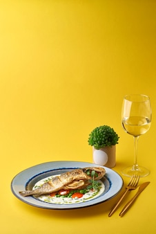 Tasty cooked fish with french sauce based on white wine and fresh vegetables