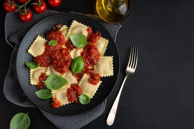 토마토 소스와 바질과 함께 맛있는 요리 이탈리아 라비올리가 어두운 접시에 제공됩니다.