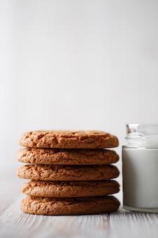 Вкусное печенье и стакан молока в прозрачном стакане на деревенском белом фоне с копией пространства