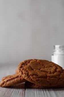 素朴な白い背景の上の透明なガラスのおいしいクッキーとミルクのガラス