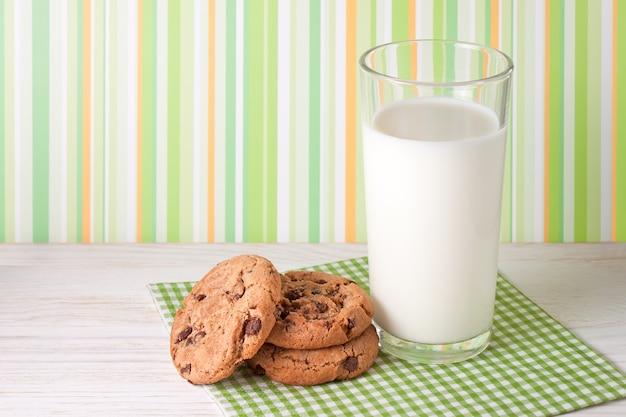 白い木の表面とカラフルな背景においしいクッキーと牛乳のガラス