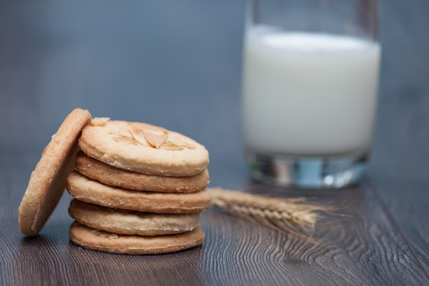 Tasty cookies biscuits with almond and wheat on the plate on  wooden background with glass