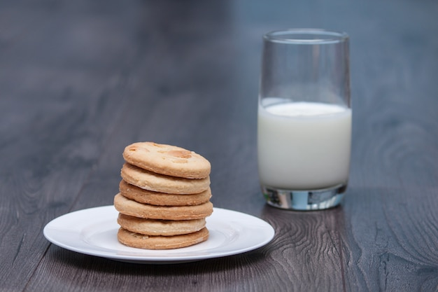 Tasty cookies biscuits with almond on the white plate on the wooden background with glass