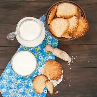 Tasty cookies and glass of milk on rustic wooden