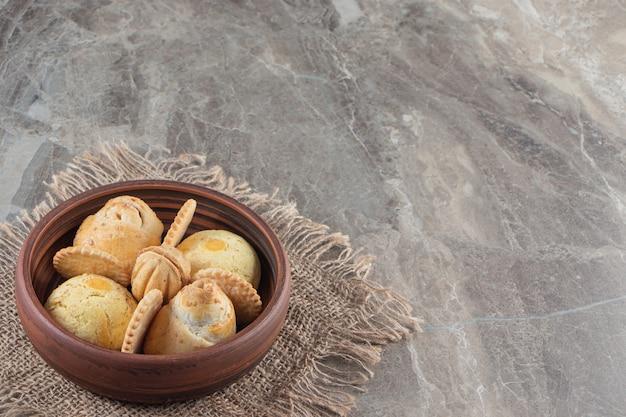 Вкусное печенье в миске по текстуре, на мраморе.