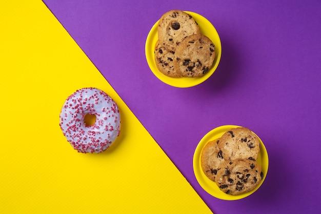 Вкусное печенье с шоколадной крошкой и глазированным пончиком на цветном фоне