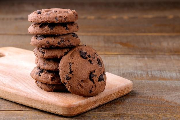 茶色の木製テーブルのボードにチョコレートとおいしいクッキー
