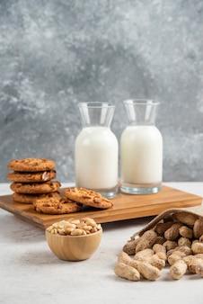 나무 판자에 유기농 땅콩과 우유 한 잔을 곁들인 맛있는 쿠키.