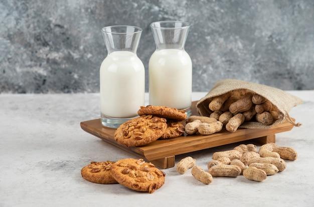 나무 판자에 우유 한 잔과 함께 유기농 땅콩과 꿀을 넣은 맛있는 쿠키.