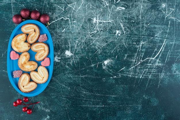 블루 보드에 설탕 젤리 사탕과 함께 맛있는 쿠키. 고품질 사진