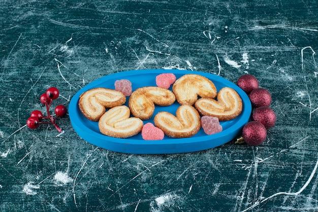 青いボードに砂糖のゼリーキャンディーが入ったおいしいクッキー。高品質の写真