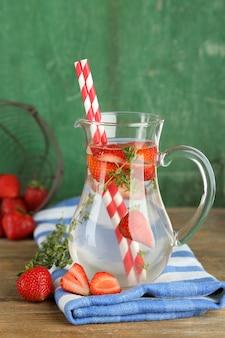 Вкусный прохладный напиток с клубникой и тимьяном на деревянном столе