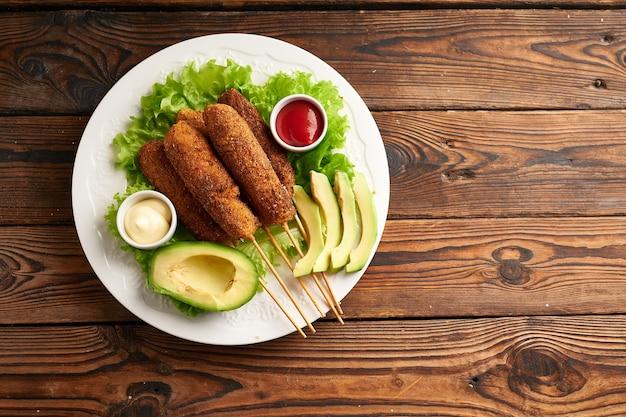 木製のテーブルの白いプレートにソースとサラダを添えたおいしいアメリカンドッグ