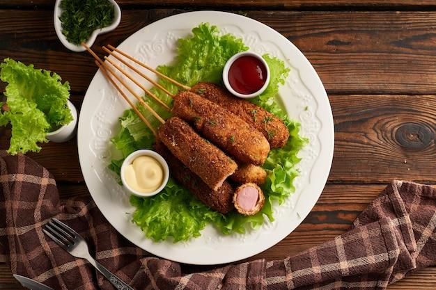 Вкусный корн-дог с соусом и салатом подается на белой тарелке на деревянном столе