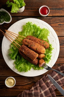 Tasty corn dog with sauce and salad served on white plate on wooden table