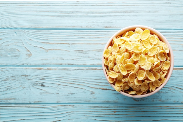 Tasty corn flakes in glass bowl on blue background. place for text. top view, flat lay.