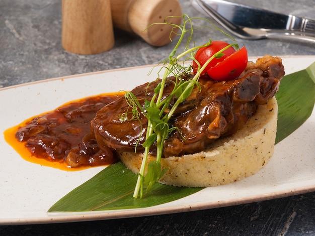 Вкусный кус-кус с бараниной с соусом, украшенный микрозеленью