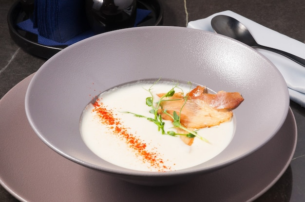 Tasty cream cheese soup decorated with paprika jamon micro greenery