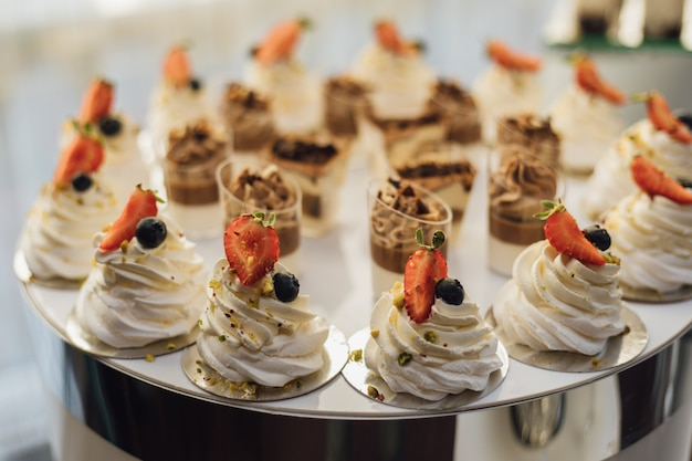 Tasty creamy desserts decorated with strawberry slices and tiramisu