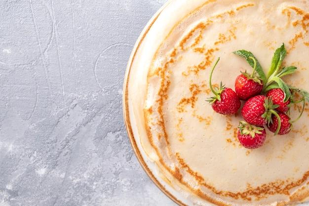 Вкусный креп со свежей клубникой на тарелке вид сверху, копией пространства