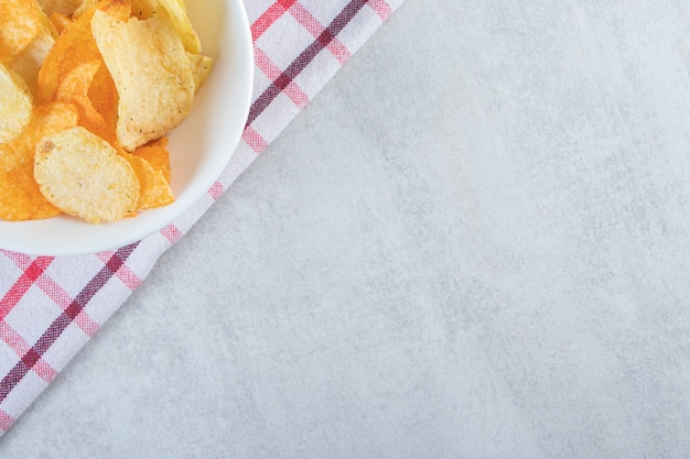 Tasty crispy chips placed in white bowl with tablecloth.