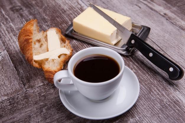 一杯のコーヒーとバターの横にあるおいしいクロワッサン。甘い朝食。