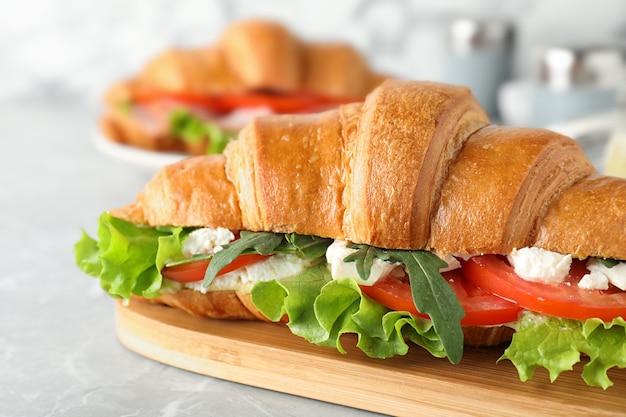 밝은 회색 대리석 테이블에 페타 치즈와 토마토를 넣은 맛있는 크루아상 샌드위치