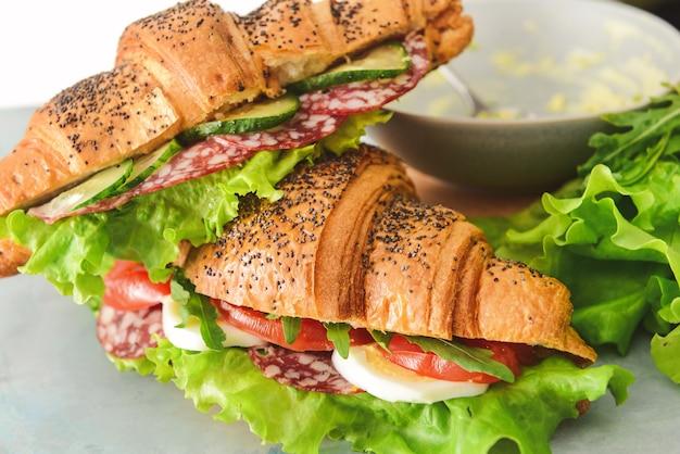 Вкусные бутерброды с круассаном на столе