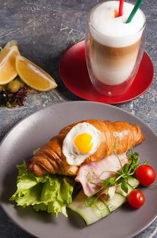 Вкусный круассан с ветчиной и кофе латте concept breakfast