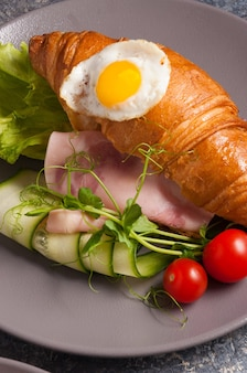 Tasty croissant with ham cucumber and egg concept breakfast