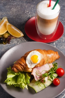 Tasty croissant with ham and latte coffee concept breakfast